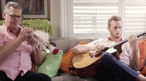 Two people playing a trumpet and a guitar