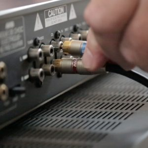 Close up of someone plugging in wires into the back of a receiver