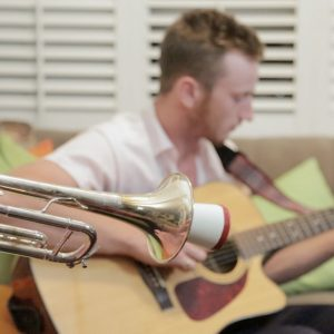 Focus on a trumpet, with a man playing an acoustic guitar out of focus