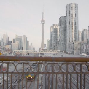A shot of the Toronto skyline on a bridge over train tracks