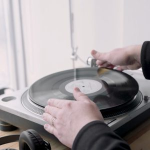 Someone putting on a vinyl record